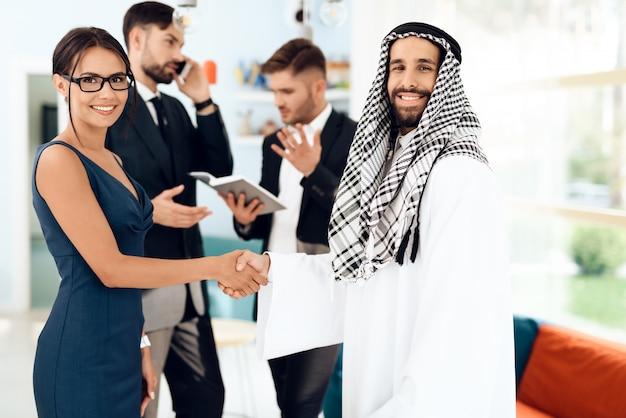 Um homem em roupas árabes e uma menina estão apertando as mãos.