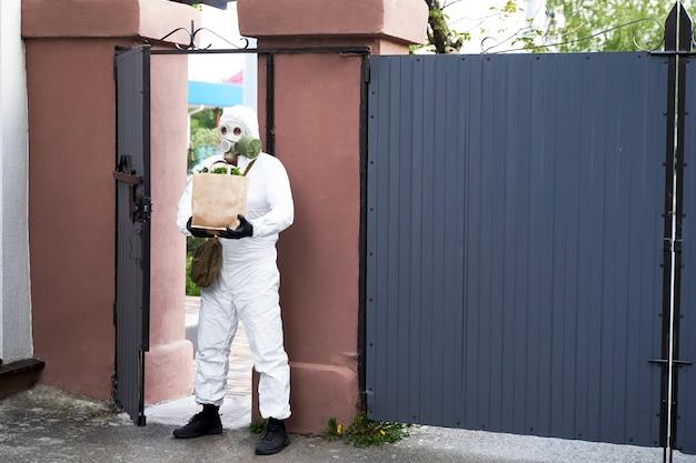 Um homem em roupas de proteção e uma máscara de gás trouxe comida