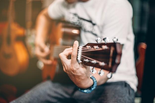 Um homem em t-shirt branca tocar música por guitarra acústica