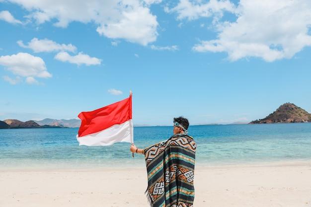 Um homem em tecido tradicional acenando com a bandeira da indonésia na praia