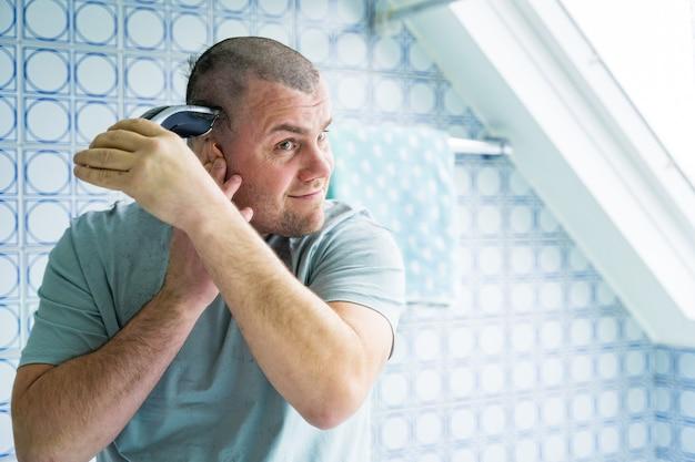 Um homem em um banheiro e se barbeando com um barbeador eletrônico