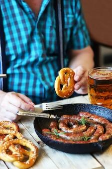 Um homem em um bar come linguiça e pretzels com cerveja.