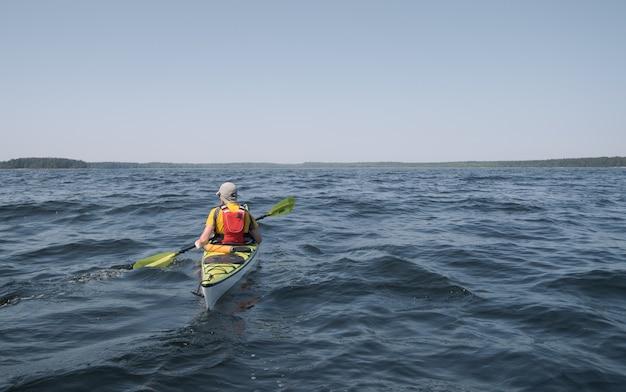 Um homem em um caiaque desliza na superfície da água. tema de esportes aquáticos