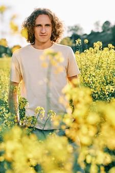 Um homem em um campo de colza olhando para a câmera em um dia de primavera