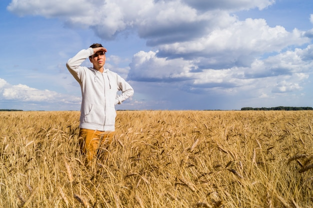 Um homem em um campo de trigo olha para o futuro