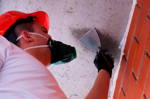 Um homem em um capacete e um respirador executa o trabalho de pintura em um teto concreto, contra um fundo da alvenaria.