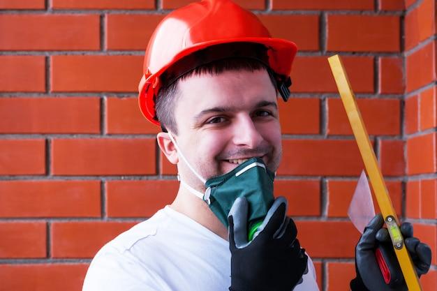 Um homem em um capacete protetor usa um respirador no contexto de uma parede de tijolo vermelho.