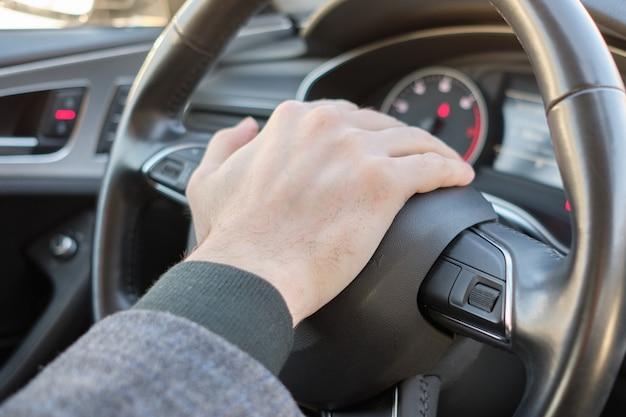 Um homem em um carro moderno. a mão pressiona o sinal sonoro e emite um sinal.