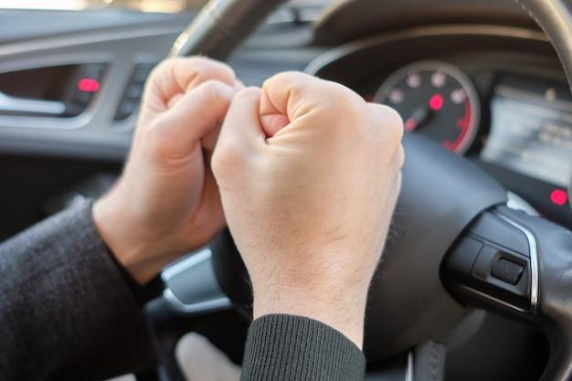 Um homem em um carro moderno. mãos batendo no volante com raiva.