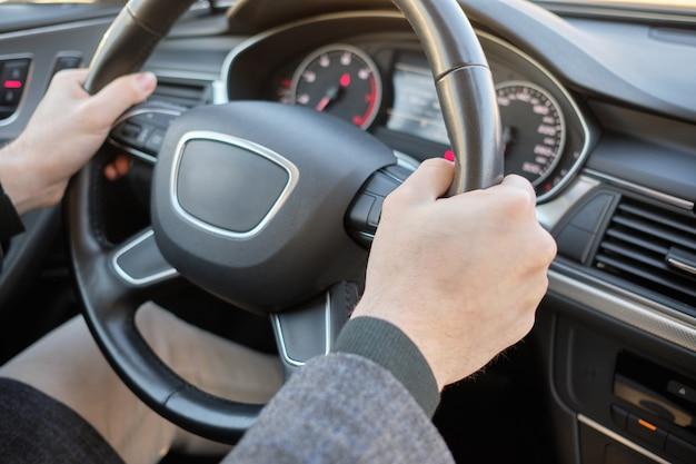 Um homem em um carro moderno. mãos segurando o volante no local correto.
