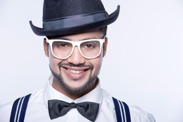 Um homem em um chapéu e óculos está sorrindo.
