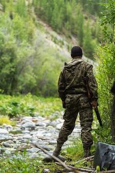 Um homem em um comuffle com um rifle nas mãos olha para frente. caça ao pato.