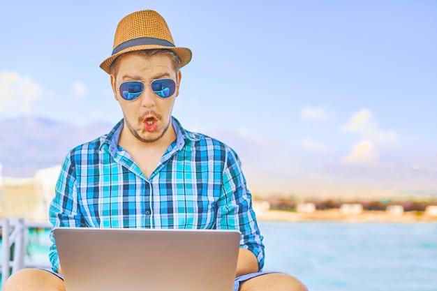 Um homem em um dia ensolarado em um cais pelo mar, surpreendido por algo no laptop.