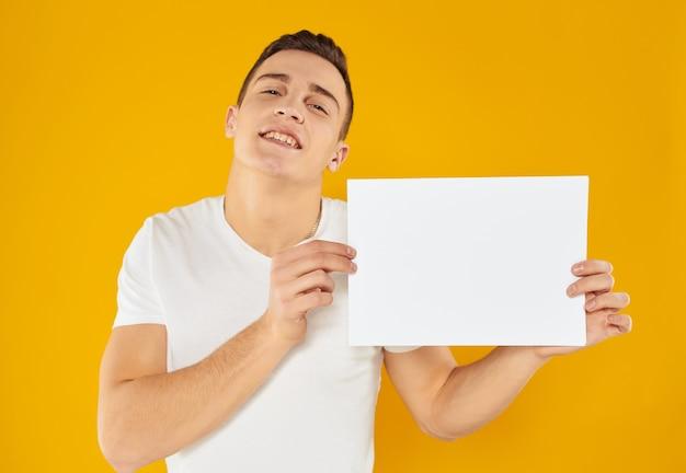 Um homem em um fundo amarelo com uma maquete na mão uma folha de papel branca