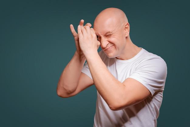 Um homem em um fundo azul em mãos dadas perto de seus olhos como um telescópio peeps