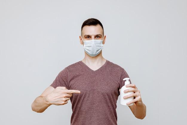Um homem em um fundo branco usando uma máscara de higiene usa um desinfetante para as mãos para evitar infecções por gripes, resfriados ou coronavírus.