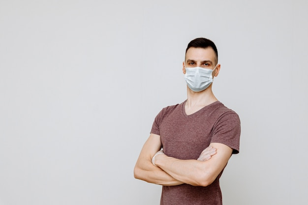 Um homem em um fundo branco, vestindo uma máscara de higiene para evitar infecções por gripes, resfriados ou coronovírus.