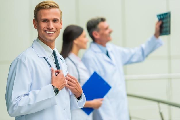 Um homem em um médico de jaleco branco levanta e sorri.