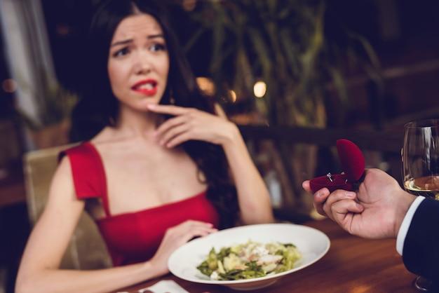 Um homem em um restaurante faz uma oferta a uma garota.