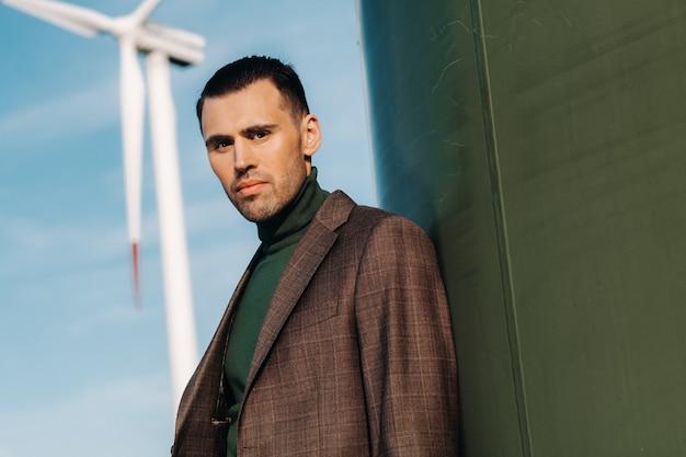Um homem em um terno com uma camisa verde golf está ao lado de um moinho de vento contra o fundo do campo e o céu azul