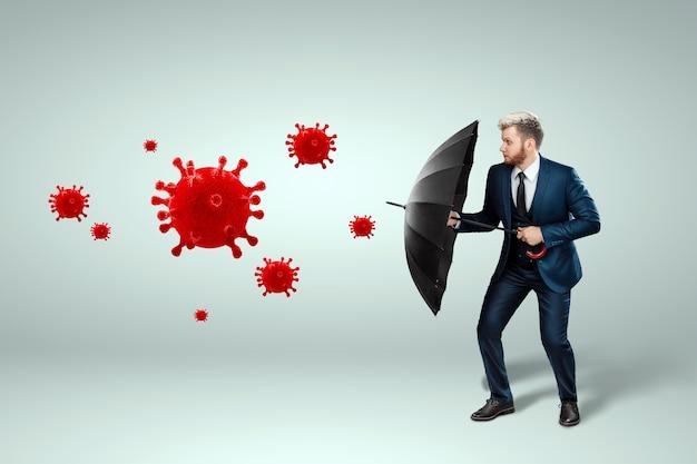 Um homem em um terno de negócio está com um guarda-chuva nas mãos e protege seu negócio do coronavírus