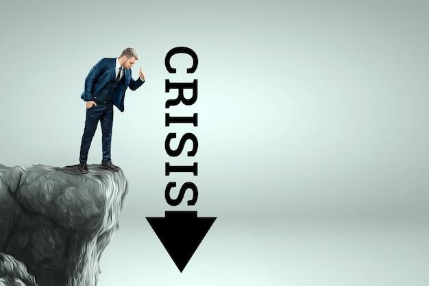 Um homem em um terno de negócio está de pé na beira de um penhasco e olha para uma flecha com a inscrição crise