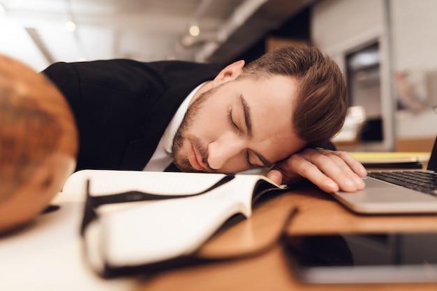 Um homem em um terno de negócio está dormindo no local de trabalho.