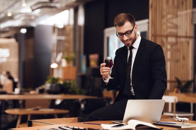 Um homem em um terno de negócio está segurando um copo de vinho na mão.