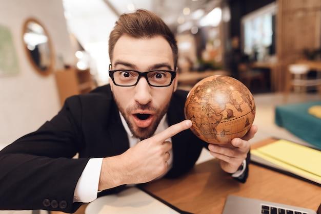 Um homem em um terno de negócio está segurando um globo nas mãos dele.
