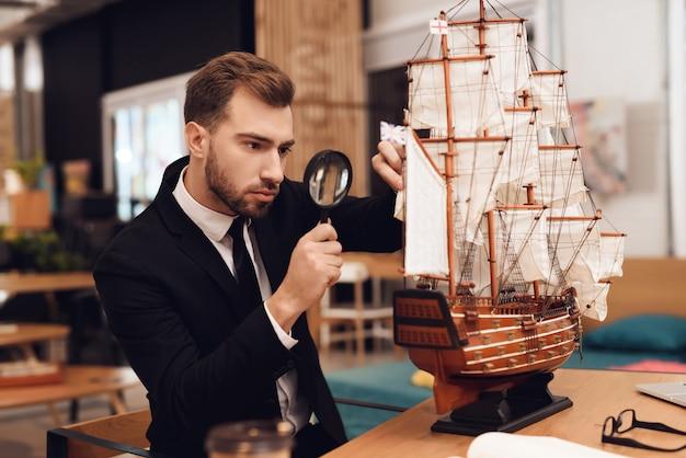 Um homem em um terno de negócio está sentado à mesa com um veleiro.