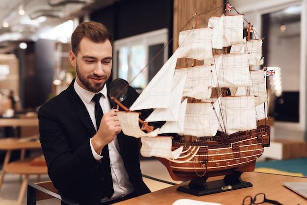 Um homem em um terno de negócio está sentado em uma mesa com um veleiro.