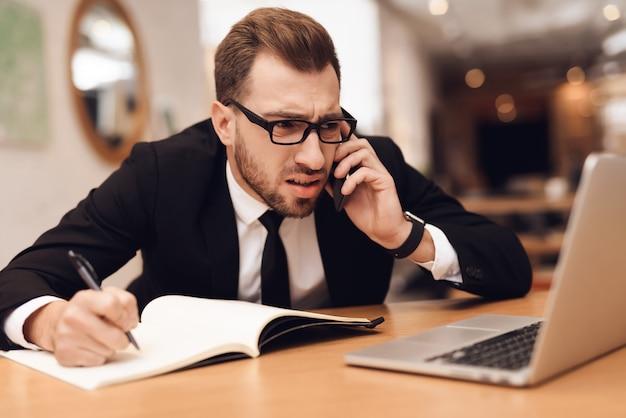 Um homem em um terno de negócio está trabalhando em seu escritório.