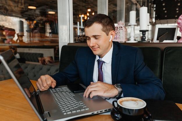 Um homem em um terno de negócio trabalha em um laptop em um café. empresário com laptop.