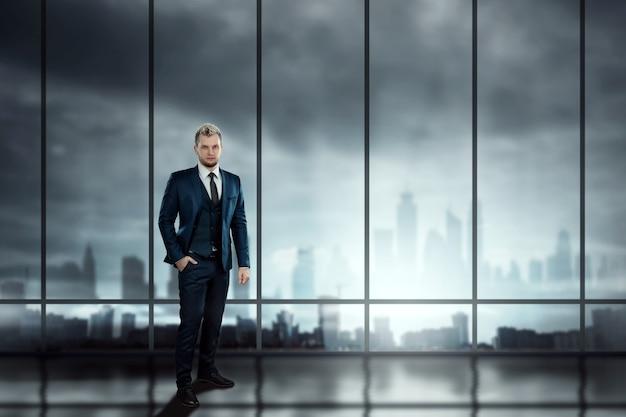 Um homem em um terno de negócio, um empresário em pé contra o fundo de grandes janelas com vista para a cidade, olha para longe