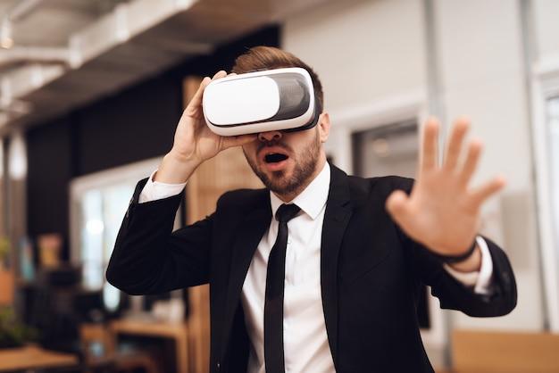 Um homem em um terno de negócios, olhando para uma realidade virtual.