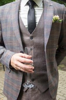 Um homem em um terno de três peças segura um copo
