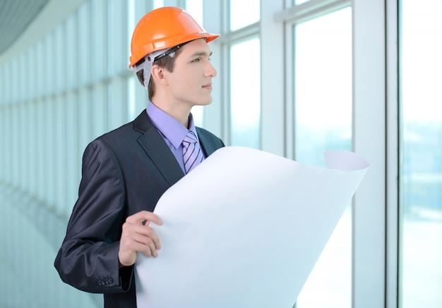 Um homem em um terno e capacete olha para um plano de construção.