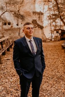 Um homem em um terno formal, o noivo está na floresta de outono, ele mantém as mãos nos bolsos