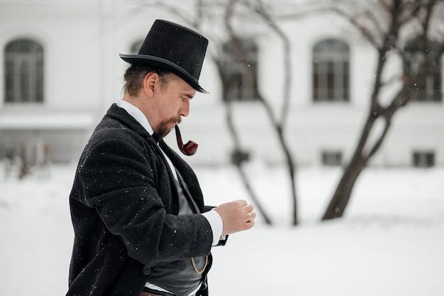 Um homem em um terno vintage acende um cachimbo