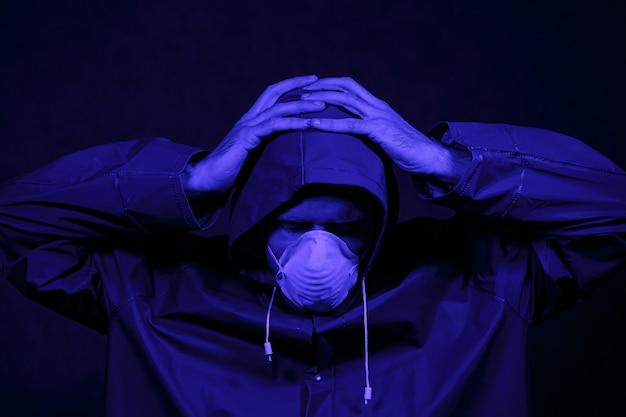 Um homem em um traje de proteção e máscara branca em um quarto escuro. conceito de imagem de halloween. proteção contra vírus. iluminado com luzes coloridas