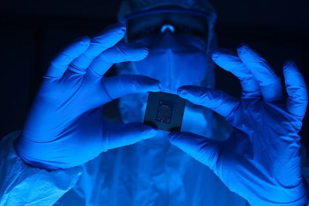Um homem em um traje de proteção tem um microchip nas mãos. trabalhador de laboratório de pesquisa usando luvas e óculos de segurança