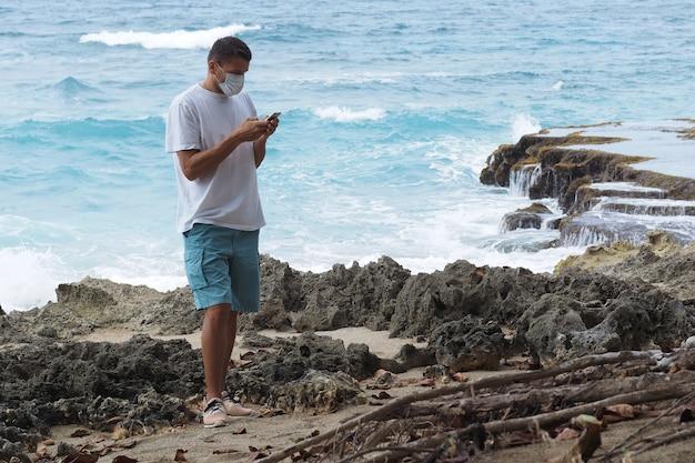 Um homem em um turista de máscara médica fica em uma costa rochosa do oceano com um telefone celular.