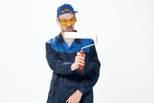 Um homem em um uniforme de trabalho pintando as paredes reparando a casa