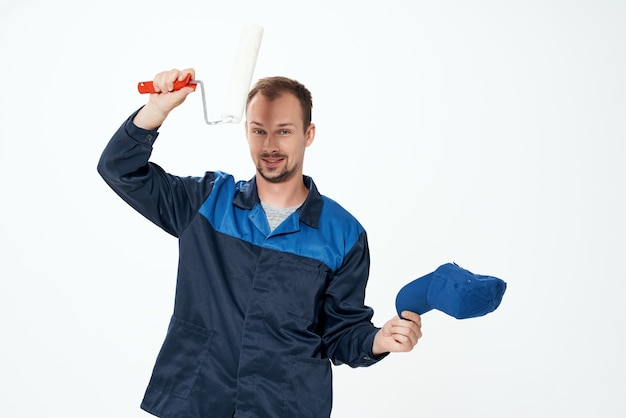 Um homem em um uniforme de trabalho um rolo para pintar paredes em suas mãos, conserto de decoração