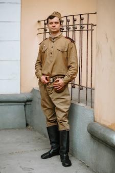 Um homem em um uniforme soviético da segunda guerra mundial fica na parede amarela