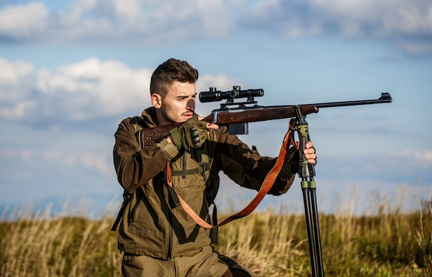 Um homem em uma caçada segura uma arma e aponta para sua presa.