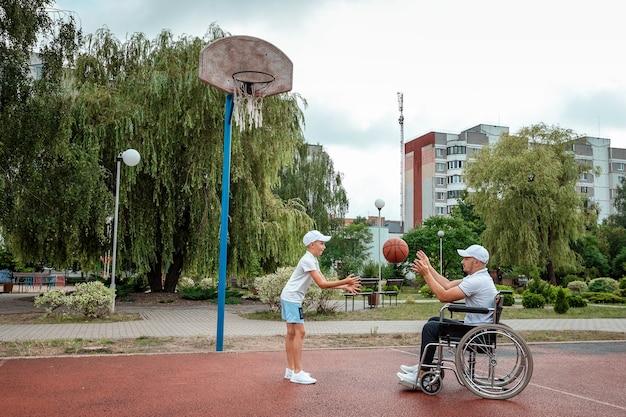Um homem em uma cadeira de rodas joga basquete com o filho no campo de esportes. pai com deficiência, infância feliz, conceito de pessoa com deficiência.