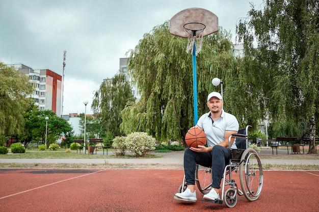 Um homem em uma cadeira de rodas joga basquete no campo de esportes. o conceito de uma pessoa com deficiência, uma vida plena, uma pessoa com deficiência, boa forma, atividade, alegria.