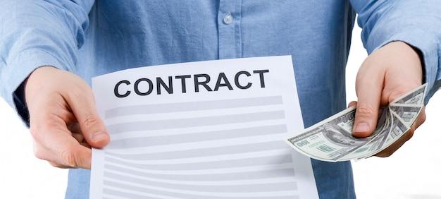 Um homem em uma camisa azul prende uma folha com um contrato e nos dólares em um fundo branco.