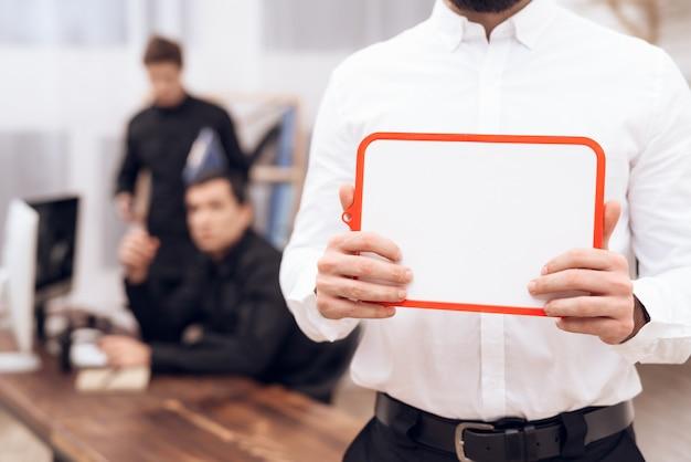 Um homem em uma camisa branca está de pé com uma placa branca.